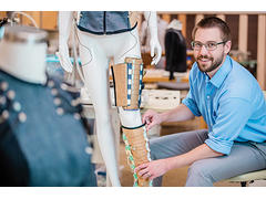 Brad Holschuh fitting compression material on a mannequin leg.