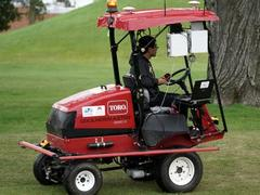 A red Toro mower with a man driving it.