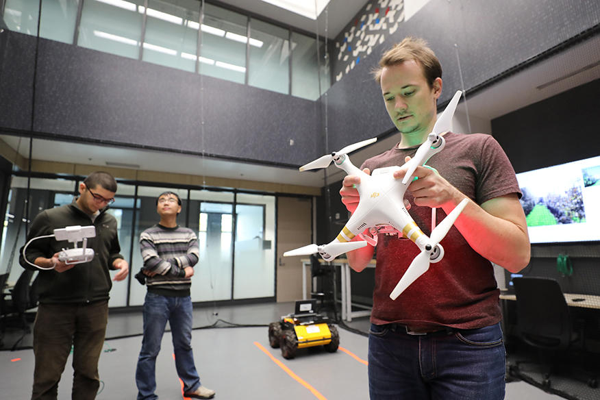 Student holding a drone inside a lab.
