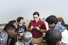 A graduate student showing a group of middle schoolers a robotic bug.