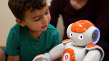 A boy sitting with a robot.