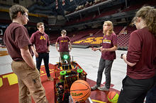 Five students gathered around a robot on a basketball court.